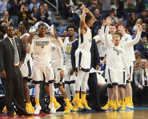 West Virginia basketball players celebrate in the closing moments of their 83-71 win over Notre Dame in a second-round NCAA Tournament game Saturday in Buffalo. AP photo