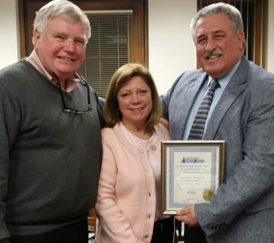 Pictured, from left, is Gregory Peterson, village attorney; Cindy Peterson, his wife; and Mayor James Rensel. Submitted photo