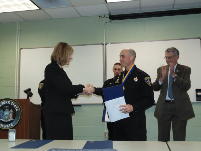 State Sen. Cathy Young, R-Olean, gives deputy Jason Beichner the Liberty Medal during a ceremony at the county Emergency Services Office. The medal is the highest recognition bestowed by the State Senate.
