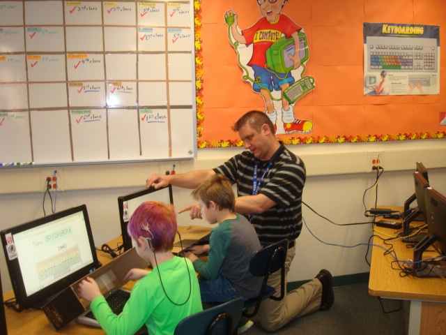 Teacher Mark Putney is pictured giving computer instruction to second-grade students Henry Conroy and Jazz Witkowski.