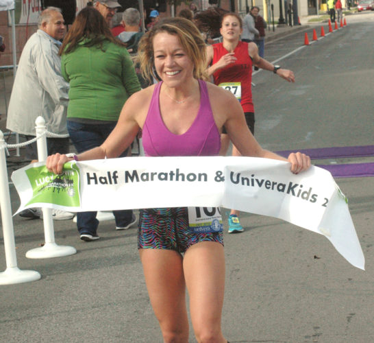 Brooke Adams is all smiles after crossing the finish line at the Lucy Town Half Marathon last October in Jamestown. P-J file photo by Scott Kindberg