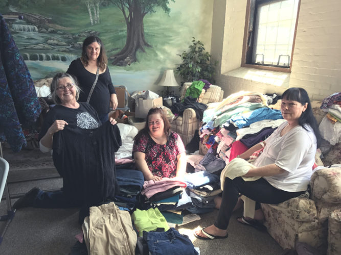 "Realife Church, Praise Fellowship and Community Helping Hands are gearing up once again to host the ""Treasured Gems"" event on April 29. Pictured from left are Shari Grice, Treasured Gems event coordinator; Danette Battle, volunteer; Jodie Thomas, volunteer; and Judy Atwater, volunteer, as they sort out clothes for the upcoming event.  P-J photo by Katrina Fuller"