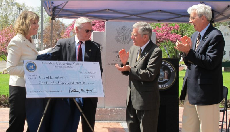From left, state Sen. Cathy Young; Chuck Telford, Veterans Memorial Park commission chairman; Jamestown Mayor Sam Teresi; and state Assemblyman Andy Goodell revealing Friday the ceremonial check for $100,000 from the state that Young secured for improvements to Veterans Memorial Park, located on West Third Street near Logan and Harding avenues. P-J photo by Dennis Phillips
