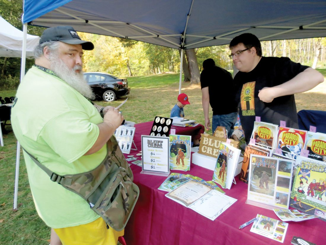 "Paranormal investigator Thomas Curtin (left) buys a ""Bluff Creek"" keychain from Jordan Lowe during Sunday's Bigfoot Day at Beaver Creek State Park. Lowe, the proprietor of Asylum Comics in Marietta, Ohio, has written a comic book on the life of a young Bigfoot. (Photo by Stephen Huba)"