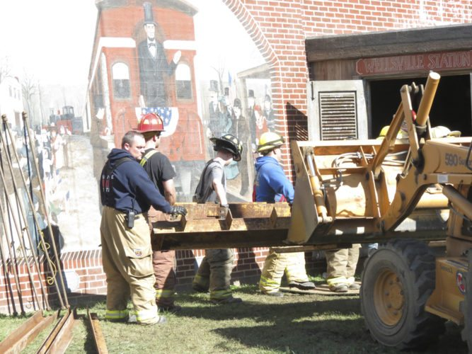 Behind the backhoe pictured, members of several fire departments put away pieces of Wellsville's flood wall in its storage facility following a training session conducted Sunday morning. The Wellsville Fire Department hosted the training session, while fire crews from Highlandtown, Irondale, Liverpool Township and Calcutta also participated in the session. (Photo by Steve Rappach)
