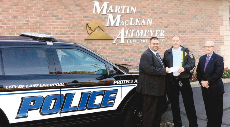 "Funeral Director Matthew Watson (left) and General manager Mike Sigler (right) present East Liverpool Police Chief John Lane with a donation for his department's ""Cops and Kids"" program. (Submitted photo)"