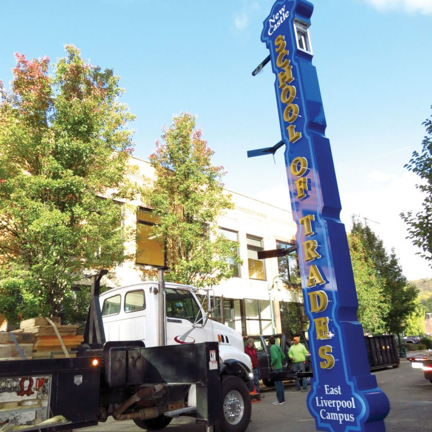 A 27-foot vertical sign for the New Castle School of Trades dangles from a crane on Tuesday morning as workers prepare to install it on the southeast corner of the former Ogilvie's Department Store, 129 E. Fifth St. The sign has illuminated letters. (Photo by Stephen Huba)