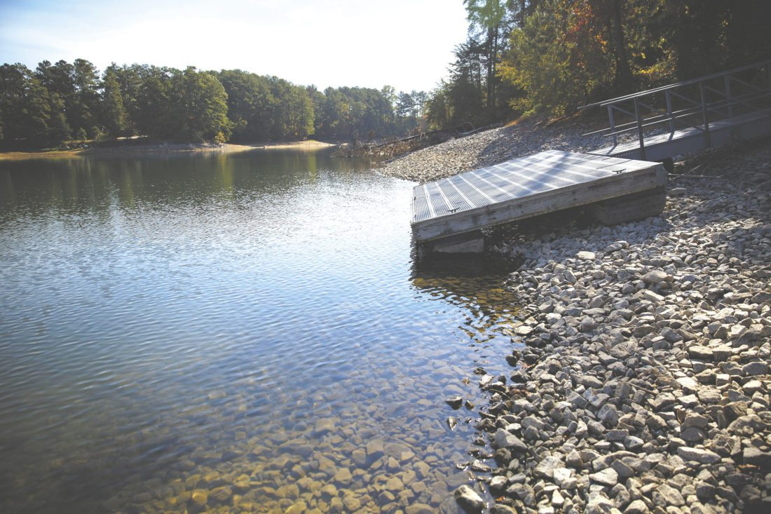 In this Wednesday, Oct. 26, 2016 photo, a floating dock sits on the shore as Lake Lanier water levels recede about eight feet below normal in Buford, Ga. Some of the South's most beautiful mountains and valleys this fall are filled with desperation, as a worsening drought kills crops, threatens cattle and sinks lakes to their lowest levels in years. (AP Photo/David Goldman)