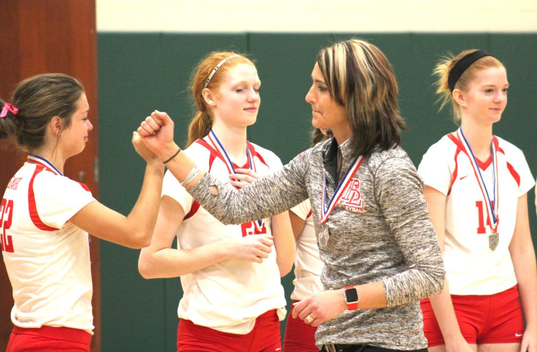 Beaver Local coach Sarah Lowe gives a fist bump to Megan Buchheit (22) after Saturday's district final match at Malvern High School. Also shown are Madison Smith (24) and Abby Jackson (14). (Photo by Joe Catullo)