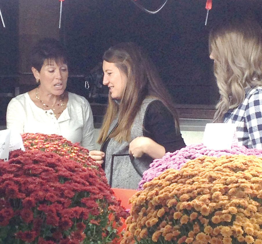 Linda Garwood, wife of Landscaping and Environmental Design instructor John Garwood, talks about some of the mums in the greenhouse with Katie Kampfer and (right) Mary Jo Brown. (Photo by Deanne Johnson)