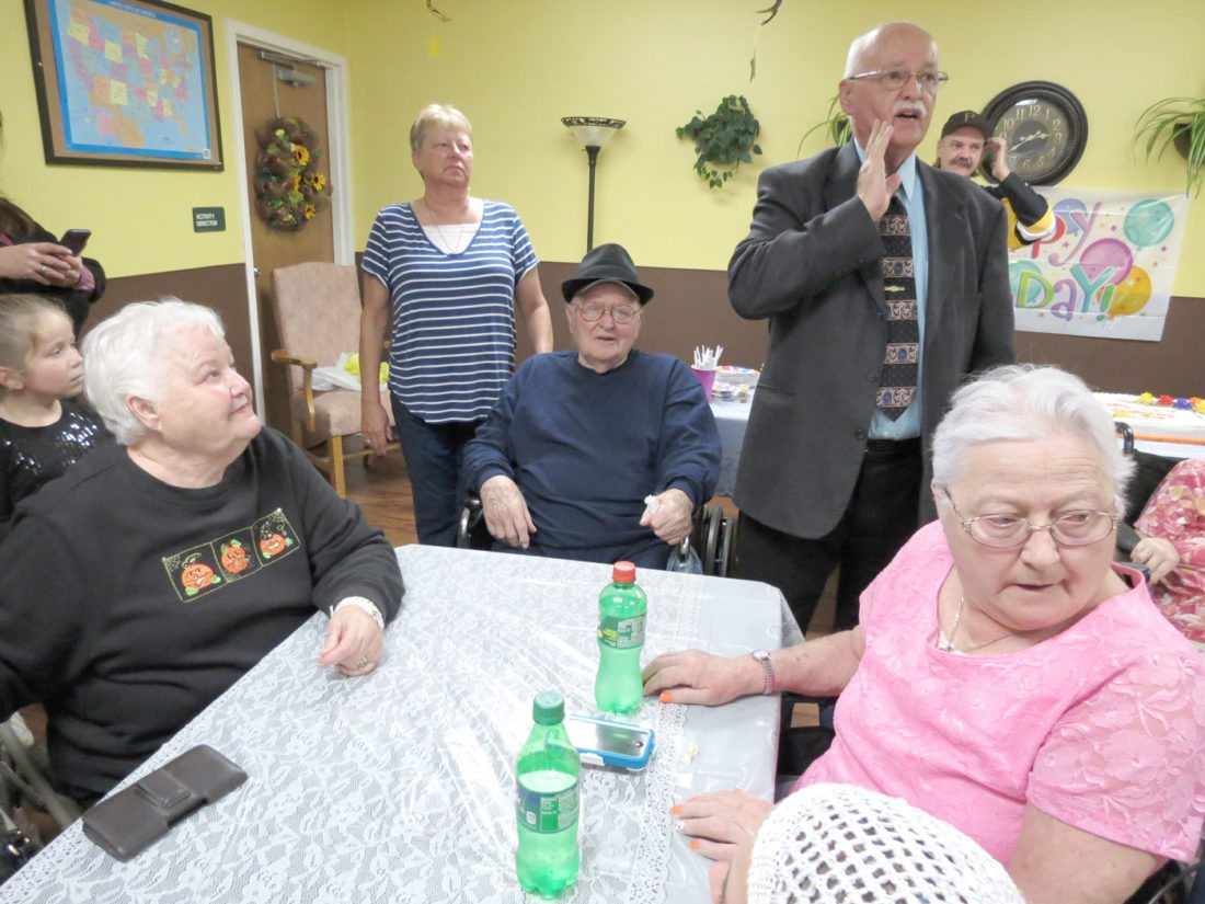 Buck Groves tries to get everyone's attention at his father Leonard Groves' birthday party on Sunday at the Calcutta Health Care Center. Leonard Groves (seated with hat on) turns 102 today. With him at the table are his daughters (from left) Peg Laughlin, of Hookstown, Pa., and Nancy Wilson, of East Liverpool. Behind him are his grandchildren, Julie Harazin, of East Liverpool, and Brandon Groves, of Chester. (Photo by Stephen Huba)