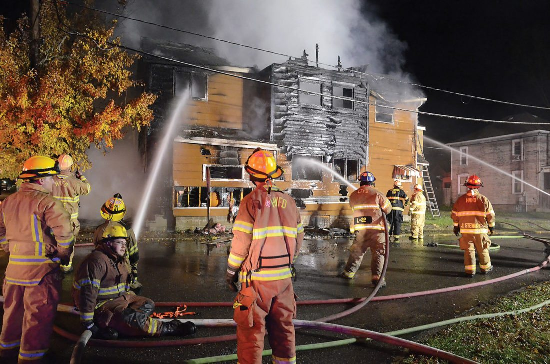 Firefighters spray water on homes that were destroyed in a fire at the corner of Commerce and Ninth streets in Wellsville late Tuesday night. (Photo by Patti Schaeffer)