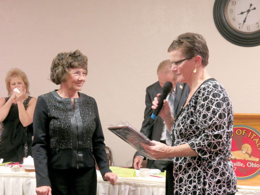 Sheryl Gibson (right), owner of Gibby's Mini Mart, viewed her plaque as she accepted the 2016 Woman of the Year Award during the Wellsville Area Chamber of Commerce's Citizens of the Year ceremony Wednesday, held at the Wellsville Sons of Italy. Presenting Gibson with the trophy was Karen Dash, a longtime teacher and former Board of Education member, who was honored as the 2015 Woman of the Year. (Photo by Steve Rappach)