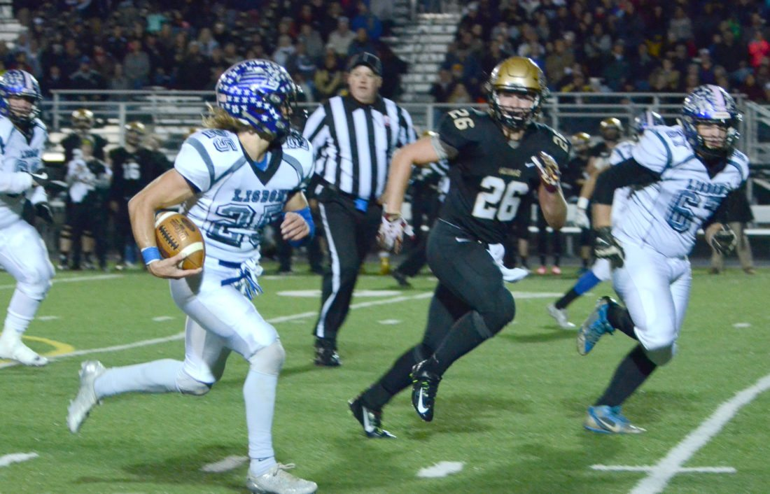Lisbon's Colin Sweeney (left) rushes for a touchdown past St. Thomas' Nathan Rich on Friday. (Photo by Patti Schaeffer)