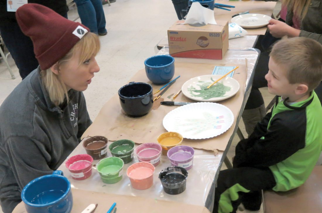 Alexa Frankovitch (left), a volunteer, talks with 4-year-old Hayden Harsh as he designs his plate at the eighth annual Paint-a-Plate event Saturday at the Wells Building in Newell. The event is hosted annually by the Homer Laughlin China Co.  (Photo by Steve Rappach)