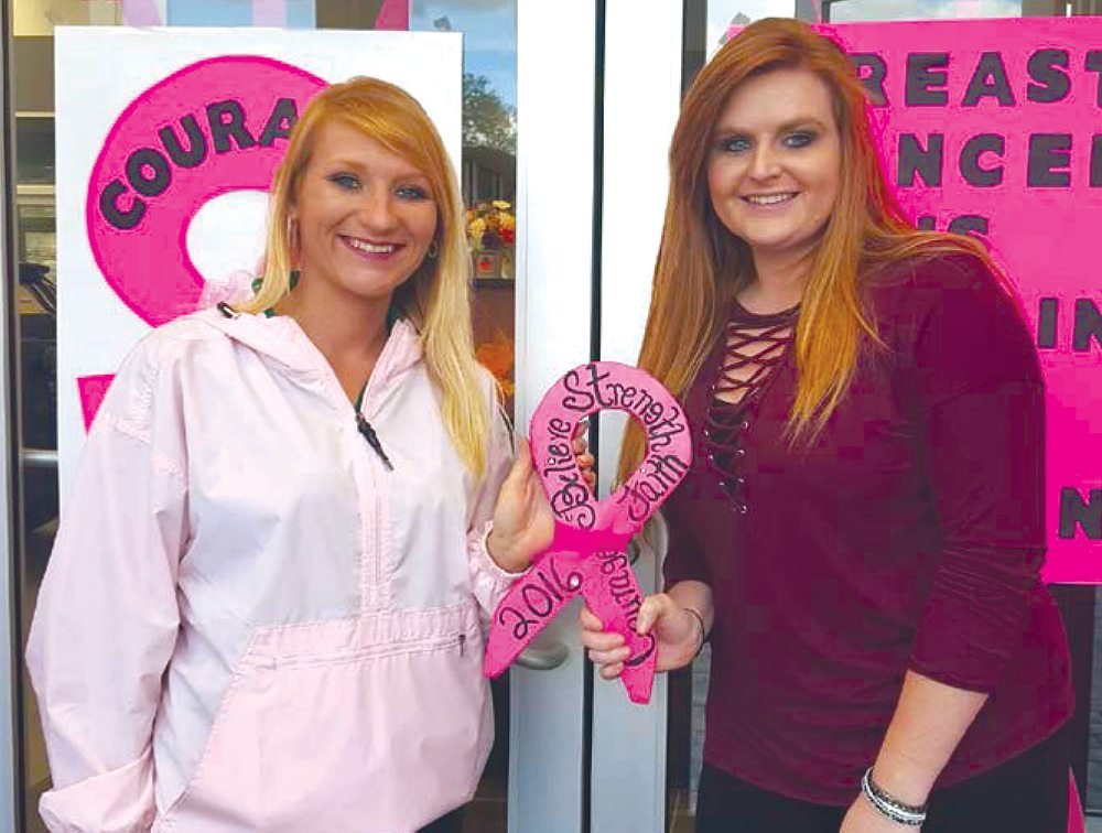 "Taylor Koper and Tracey Hall of Hancock County Chrysler Dodge Jeep Ram accepted the trophy for best decorated in Newell for CHANGE Inc.'s ""Paint the Valley Pink"" 2016 contest."