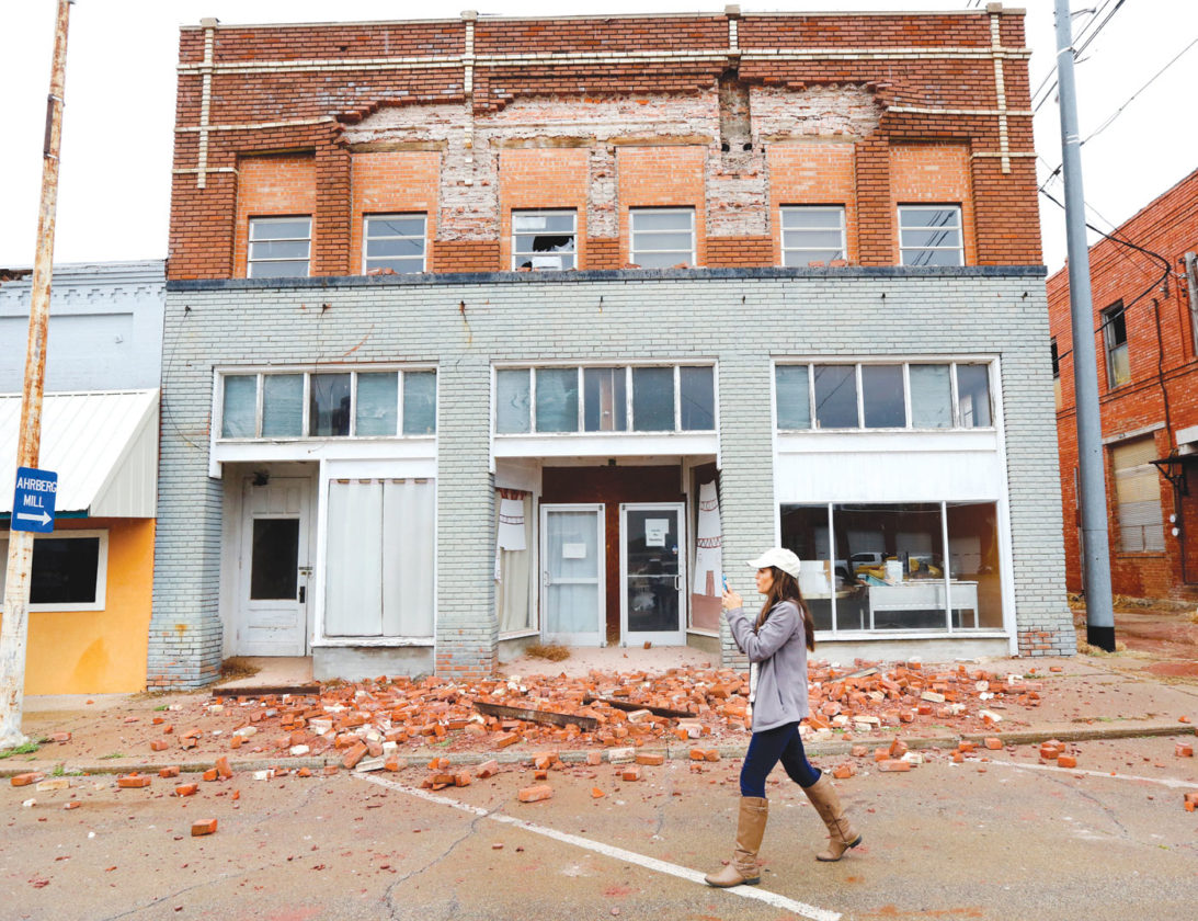 "A television reporter takes video as she walks past a damaged building in Cushing, Okla. caused by Sunday night's 5.0 magnitude earthquake, Monday, Nov. 7, 2016. Dozens of buildings sustained ""substantial damage"" after a 5.0 magnitude earthquake struck Cushing, home to one of the world's key oil hubs, but officials said Monday that no damage has been reported at the oil terminal. (Jim Beckel The Oklahoman via AP)"