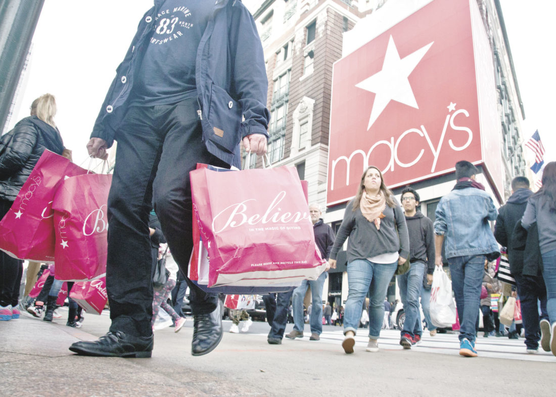 In this Friday, Nov. 27, 2015, file photo, shoppers carry bags as they cross a pedestrian walkway near Macy's in Herald Square, in New York. Thanksgiving Day shopping it isn't going away and some stores are rethinking their strategies on whether it makes sense to be open. Many major mall operators and big retailers such as Toys R Us, J.C. Penney, and Macy's are sticking with being open. Others, including the Mall of America, are closing for Thanksgiving. (AP Photo/Bebeto Matthews, File)