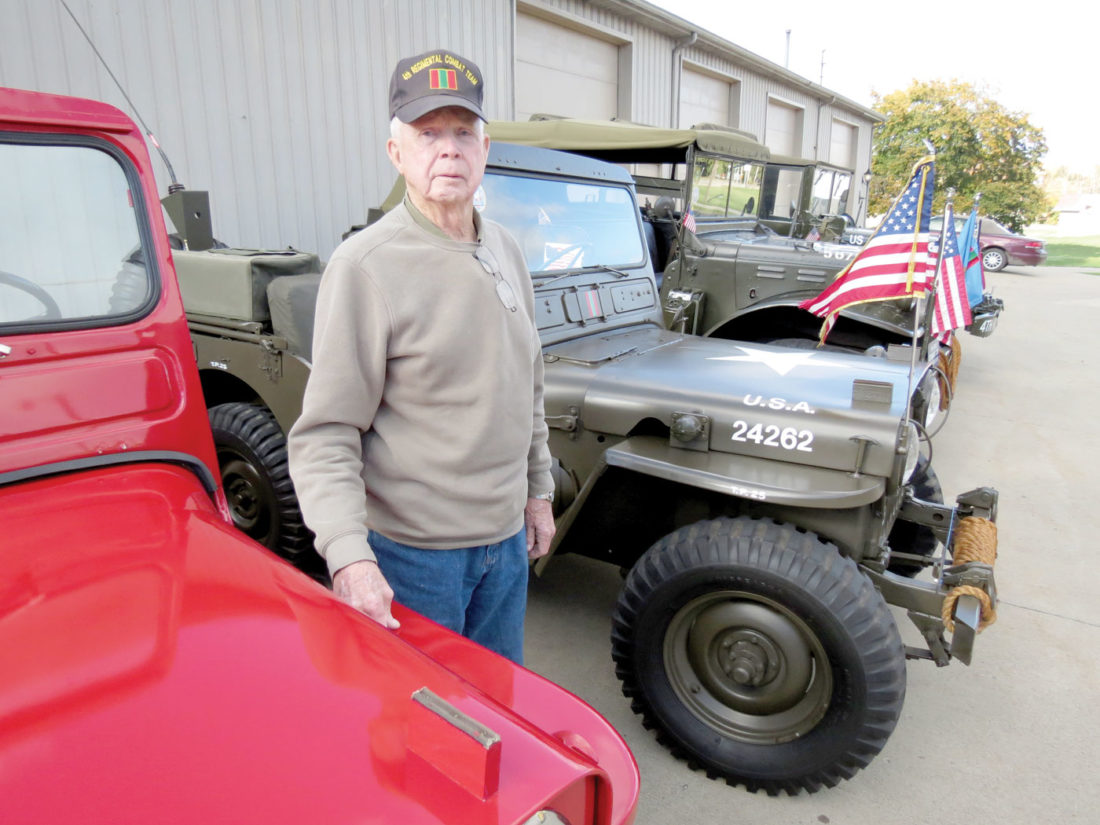Gordon Griffiths stands with his vintage military vehicles on a recent Friday outside his Glenmoor garage. He has been collecting and restoring them for about 15 years. (Photo by Stephen Huba)