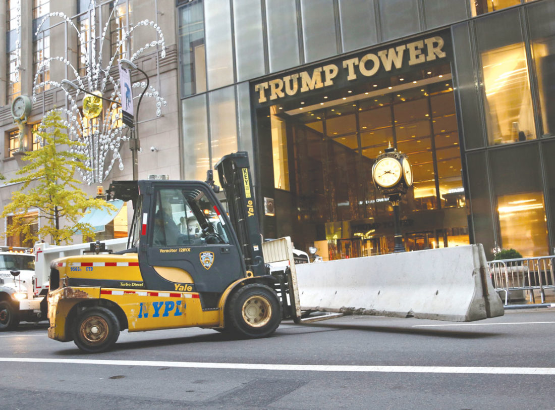 In this Nov. 9, 2016 file photo, police officers help to install concrete barriers around Trump Tower, the home of President-elect Donald Trump, in New York, Trump's neighbors are now having to navigate swarms of police officers, cement barricades, street closures and checkpoints. (AP Photo/Seth Wenig, File)