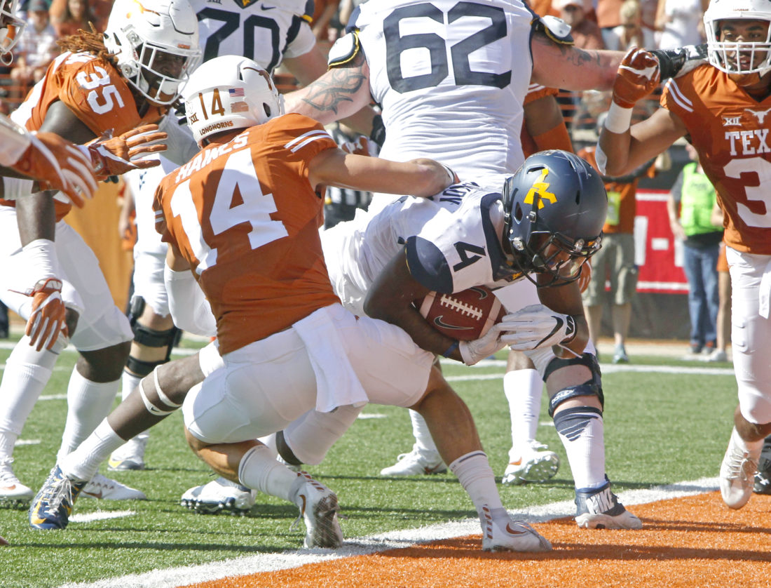 West Virginia running back Kennedy McKoy (4) runs for a touchdown against Texas' Dylan Haines (14) during the first half of an NCAA college football game, Saturday, Nov. 12, 2016, in Austin, Texas. (AP Photo/Michael Thomas)