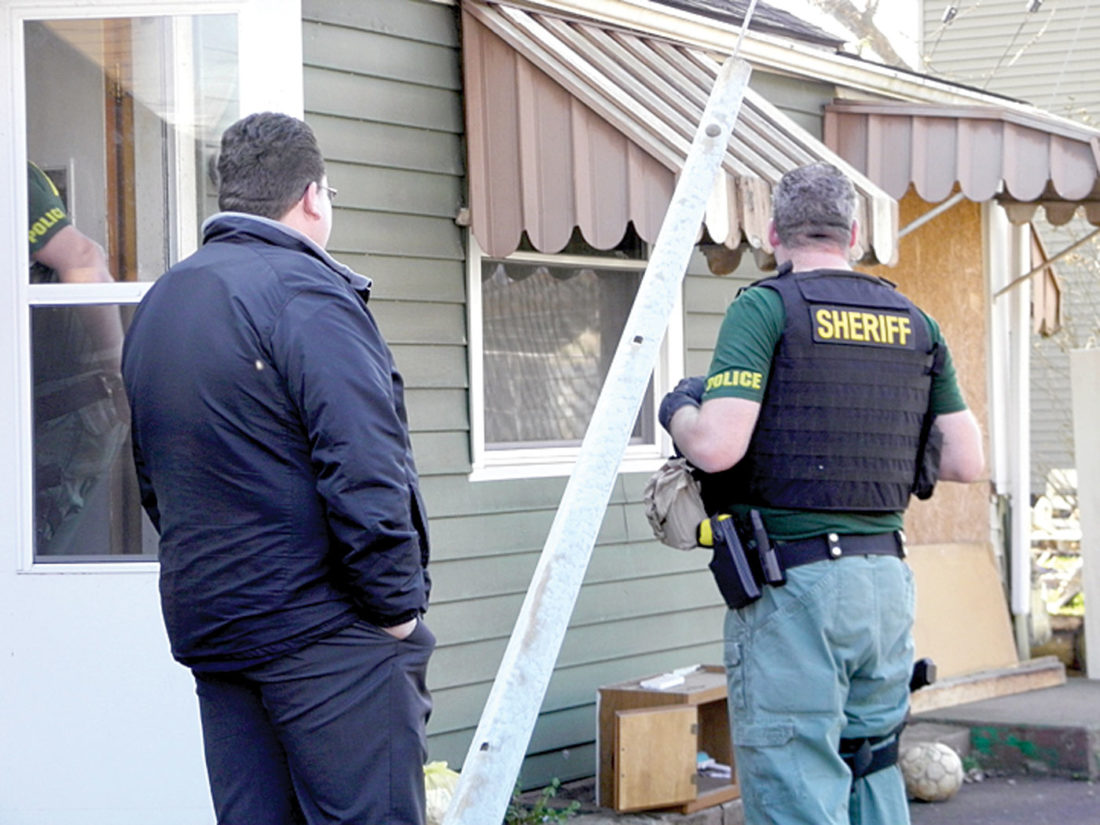A member of the county Drug Task Force and East Liverpool Service-Safety Director Brian Allen confer outside an Ohio Avenue home where a search warrant turned up drugs and weapons. (Photo by Jo Ann Bobby-Gilbert)