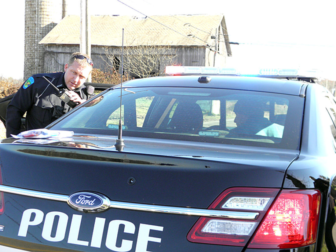 St. Clair Township Patrolman Scott Mick calls in information about suspect John Walker (seated in cruiser) after a pursuit ended in his arrest for theft and possession of drug abuse instruments. (Photo by Jo Ann Bobby-Gilbert)