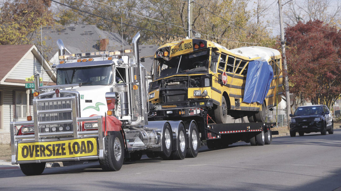 A school bus is carried away Tuesday, Nov. 22, 2016, in Chattanooga, Tenn, from the site where it crashed on Monday. The bus driver, Johnthony Walker, 24, has been arrested on charges including vehicular homicide, reckless driving and reckless endangerment. The crash killed at least five elementary school students. (AP Photo/Mark Humphrey)