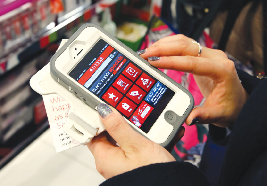 "In this Friday, Nov. 23, 2012, file photo, Tashalee Rodriguez, of Boston, uses a smartphone app while shopping at Macy's in downtown Boston. Shoppers are flocking online Monday, Nov. 28, 2016, as ""Cyber Monday"" sales hit their peak. Each year, during the busy holiday shopping weekend that kicks off on Thanksgiving and the Friday after, known as Black Friday, more and more shoppers decide to skip the mayhem in stores and shop online. (AP Photo/Michael Dwyer, File)"
