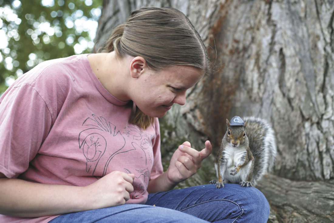 "In this Sept. 2016 photo, Penn State senior Mary Krupa plays with ""Sneezy"" the squirrel on Old Main Lawn in State College, Pa. (Phoebe Sheehan/Centre Daily Times via AP)"
