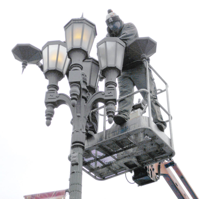 Protech Electric workers replace light bulbs in the decorative streetlights in East Liverpool. (Photo by Jo Ann Bobby-Gilbert)