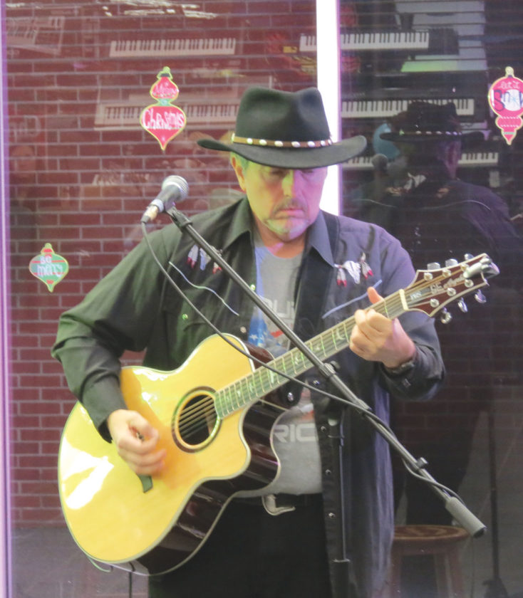 "East Liverpool-based singer/songwriter and musician Chuck Dyke performed his latest single ""The Hero at Home"" during the grand re-opening of DC Music Store Monday evening at the Dunham's Plaza in Calcutta. (Photo by Steve Rappach)"