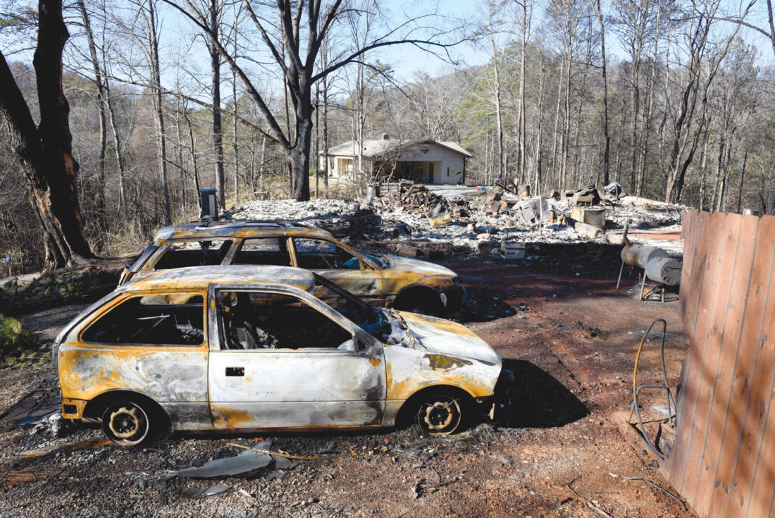 Charred home and cars sit on a property, while a neighbor's home, background, is undamaged Thursday, Dec. 1, 2016, in Gatlinburg, Tenn. A devastating wildfire destroyed numerous homes and buildings on Monday. (Michael Patrick/Knoxville News Sentinel via AP)