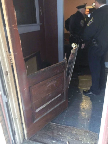 East Liverpool police officers (front to rear) Chief John Lane, Patrolman Kelsey Hedrick and Detective Greg Smith stand inside the mutilated door of 513 College Street, where a battering ram was used by the county Drug Task Force to enter. (Submittted photo)