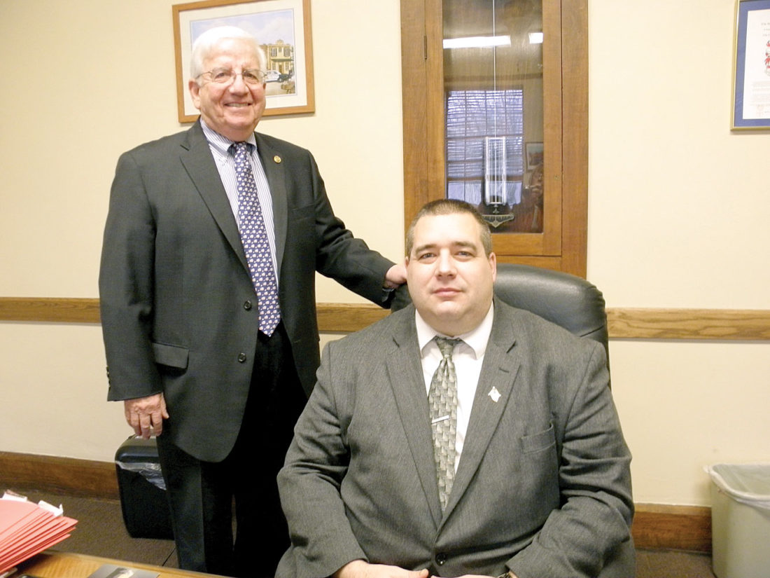 East Liverpool Mayor Ryan Stovall (seated) and local businessman Dr. Marc Hoffrichter announced Tuesday that money is now available to repair and revamp the decorative street lights in the city's downtown. (Photo by Jo Ann Bobby-Gilbert)
