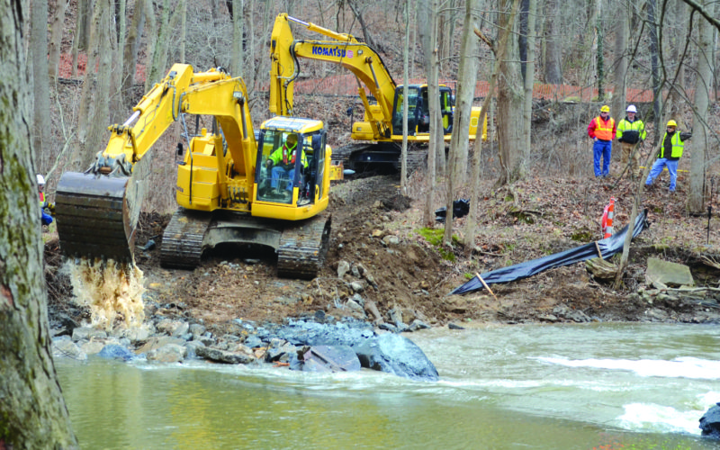 Demolition of the Willow Grove Park dam in Lisbon has begun, with an excavator from RiverReach Construction of Barberton making quick work of the structure. The $150,000 cost of the project is coming from Rutgers Organics Corp. as part of the final settlement for contamination to the Middle Fork of the Little Beaver Creek from the company's old chemical plant located upstream near Salem. The Ohio Environmental Protection Agency supports removal of the dam because it will improve stream habitat by restoring the natural flow of the creek. While the dam removal is expected to be finished soon, the restoration of the stream and adjacent area is expected to take longer. As part of the settlement, Rutgers is to donate $10,000 to Lisbon to go toward efforts to replace the wooden bridge swept away during the 2004 flash flood. (Photo by Patti Schaeffer)