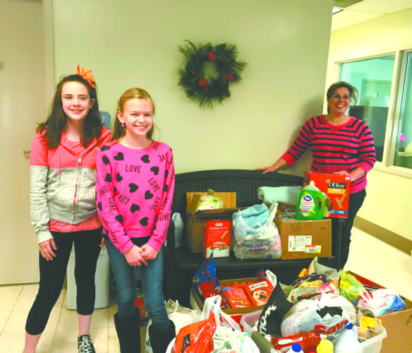"On behalf of the New Manchester Elementary School Student Council, Tia Vick and Molly Szpyrka delivered items for the Hancock County Animal Shelter, collected by the students of NMES. These items were donated in recognition of ""Spreading the Love"" on Valentine's Day to Nicole Felouzis at the Animal Shelter. (Submitted photo)"