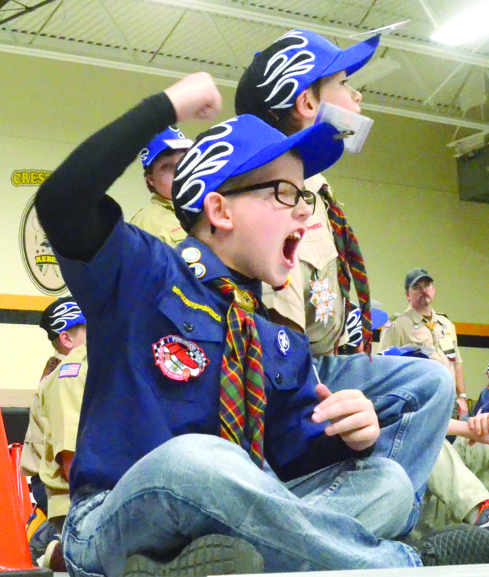 Cub Scout Hayden Patrone of Pack 40 cheers his racer down the track to an overall third place finish in the Webelos II group during the Pinewood Derby held at Crestview Middle School Saturday afternoon. Racing with Patrone is Mitchell Hofmann of Pack 102 and Jeremiah Smith of Pack 150. (Photo by Patti Schaeffer)