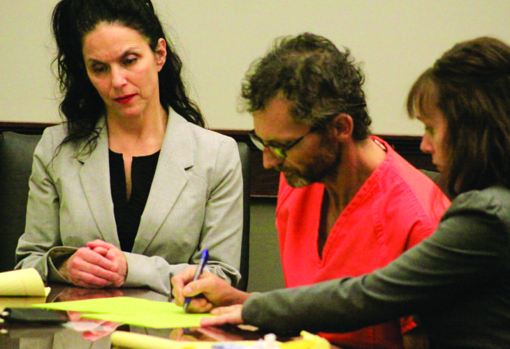 Terry Brown signs time waivers in two misdemeanor traffic cases when he was in the Columbiana County Municipal Court for a preliminary hearing for murder on Monday with his attorneys. (Photo by Deanne Johnson)