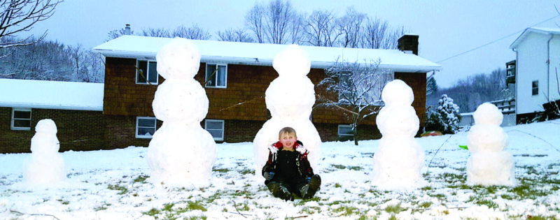 During the recent snow, Kenneth DeLauder, 8, decorated his Calcutta-Smith Ferry Road home, with a snowman family of 5 to represent his own family. Kenneth is pictured with, as snowmen (from left), 2-year-old brother Dalton, dad Ken, mom Kristy, himself, and 4-year-old brother Andrew. (Submitted photo)