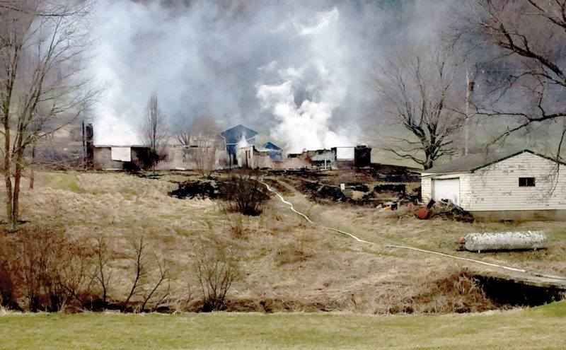 The remnants of a Tuesday fire along Route 8 in Hancock County continued to smolder Wednesday morning. (Review photo)