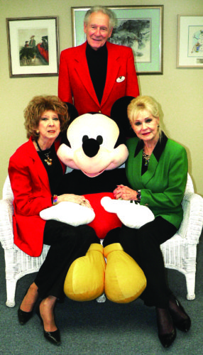 From left, Salem Storybook Museum curator Janis Yereb, former Disney senior artist Richard Theiss and his wife, Hope, gather around a large stuffed Mickey Mouse to promote Mickey at the Museum, a program to salute their Mickey Mouse collections and celebrate  Richard Theiss and his life's work from 7 to 9 p.m. Thursday at the Salem Storybook Museum inside the Kent City Center on North Lincoln Avenue. The display also will be open to the public from 1 to 6 p.m. Saturday. (Photo by Mary Ann Greier)
