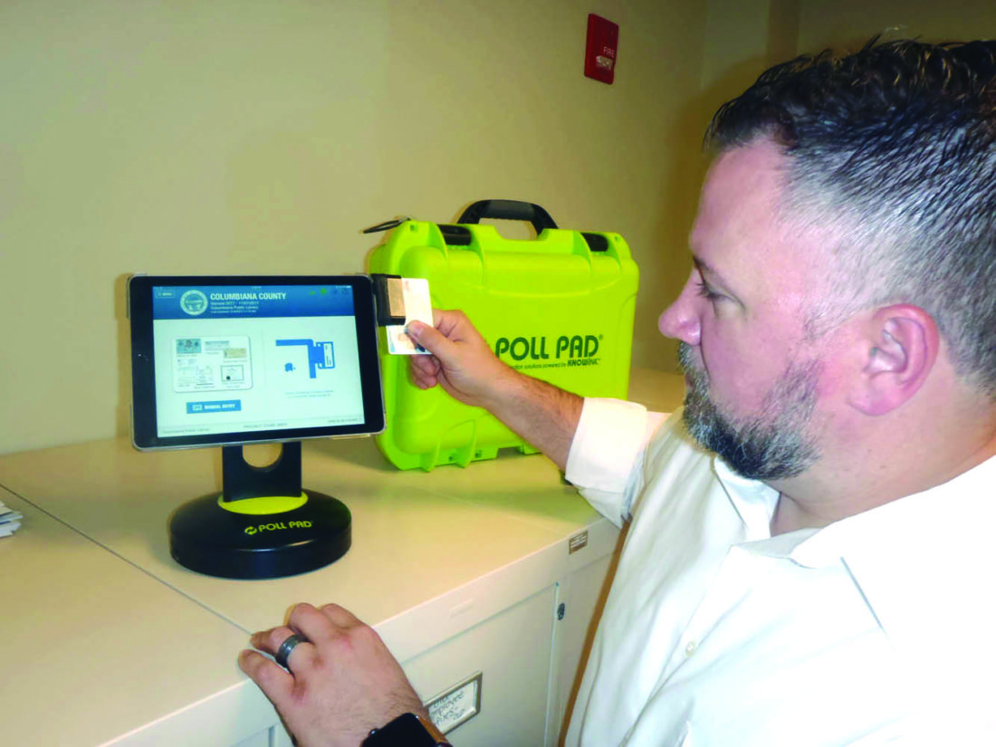 Columbiana County elections board Director Adam Booth demonstrates how the county's new electronic pollbooks will work. (Photo by Tom Giambroni)