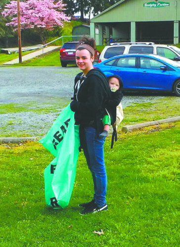 With her baby in tow, Chester resident Katelyn Woods did her share of cleaning up throughout Chester City Park Saturday morning as part of the community's clean up day, held in conjunction with West Virginia's statewide Make It Shine program. Close to 35 residents participated in the efforts as they picked up litter, swept and landscaped the city park. Some of the volunteers also started a project, consisting of painting one of the pavilions at the park, which has been partially completed and looks to be finished within the next week. Paint and landscaping supplies were donated by the Chester Beautification Committee. (Submitted photo)