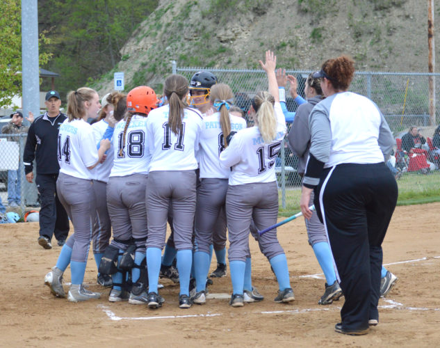 Oak Glen's Hannah Clunk is mobbed by teammates after hitting a home run against Edison on Tuesday in Wheeling. (Photo by Shawn Rine)