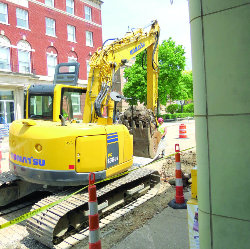 A backhoe, passing by the entrance doors of The Review, carries away the remains of a utility pole from East Fourth and Washington streets in downtown East Liverpool. Work continues weekdays on the Kent State/East Fourth Street project, which, weather permitting, is expected to be completed in late June. (Review photo)