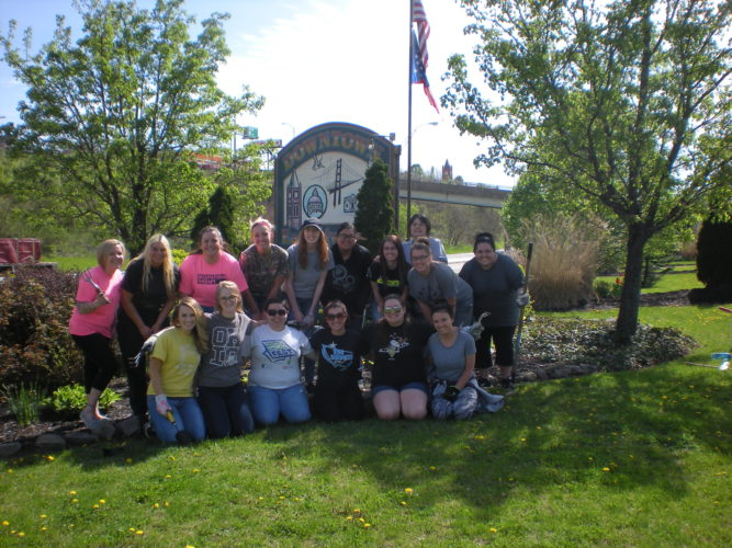 "Students from Kent State-East Liverpool's occupational therapy assistant program recently gathered at the downtown entrance ramp to the city to help spruce up the ""serpentine"" landscape by pulling weeds, trimming shrubs, raking mulch and picking up litter. This is the ninth year OTA students from the local campus partnered with the East Liverpool Area Garden Club to work on this project. Pictured are (front, from left) Lyndsie Schnieder, Shaye Starkey, Makayla Ammon, Gabrielle Fawver, Sarah Depew, Kacie Finn; and (back) Amber Crawford, Krista Messing, Hanley Spencer, Tacie Shannon, Lauren O'Leary, Jasmine Johnson, Emma Paparodis, Rebecca Little, Meika Dalrymple and Kayla Seevers. (Submitted photo)"