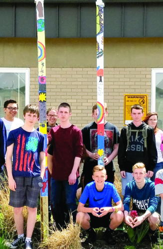 "East Liverpool High School art students, in third period drawing class, pose with a project that students in all art classes have been working on, painting posts, for the past 2 months. Mrs. Myers came up with the project after seeing it online. ""Posts for Peace and Justice"" is a growing project promoting non-violence and social justice. The mission for ""Peace and Justice"" is to build individual and community resilience, engagement through creative, cooperative, and individual expression. ""I felt my students would benefit from working together,"" Myers said. The words ""being kind, thoughtful, considerate"" of one another and our differences all were a part of the project. (Submitted photo)"