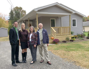 Habitat for Humanity members of the northern Columbiana County affiliate Dave Bedell (right), and Barb Loudon (next to Bedell) joined Habitat for Humanity members of the Mahoning Valley David Redig and Monica Craven on Thursday in Columbiana to announce that the two affiliates would be merging beginning Jan. 1. The group is standing in front of the last home constructed through the Columbiana County affiliate. The home is located on Beverly Drive. (Salem News photo by Katie White)