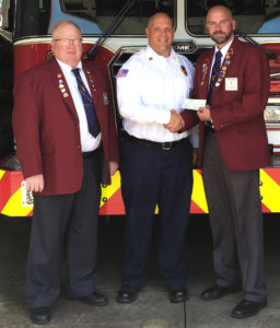 Esteemed Leading Knight Mike Mahouski, left, and Exalted Ruler Jason Green, right, give a donation of $500 from Salem Elks Lodge 305 to Salem Fire Chief Scott Mason for the department's fire safety program for children. The department uses donations to purchase educational materials through the National Fire Safety Council each year, relying on the generosity of businesses, organizations and individuals to cover the costs. (Submitted photo)
